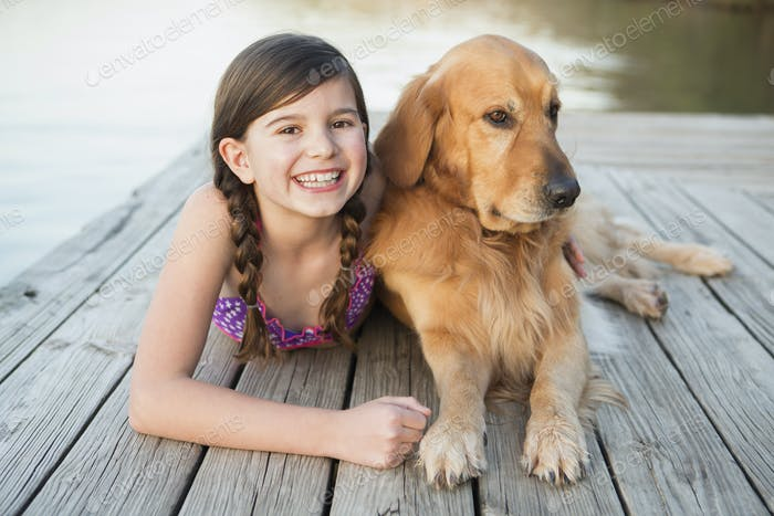 A young girl and a golden retriever dog lying on a jetty.