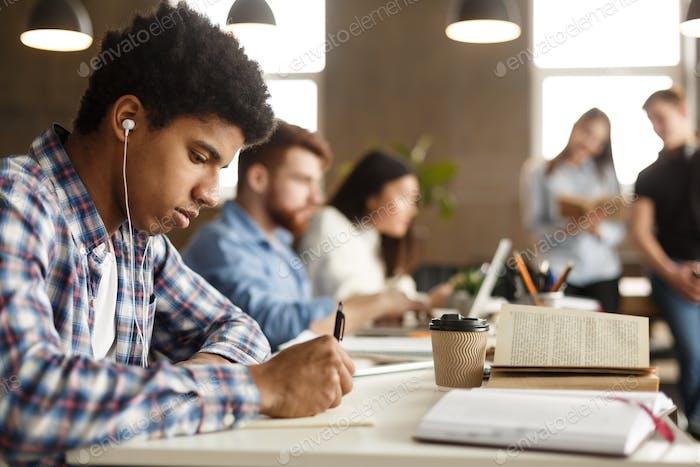 Student guy doing homework and preparing for exam