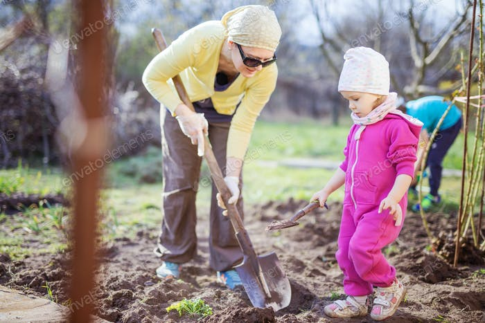 Young woman working in garden while her little daughter playing with spade beside her