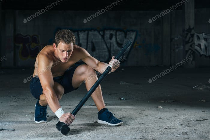 Sitting man holding sledgehammer