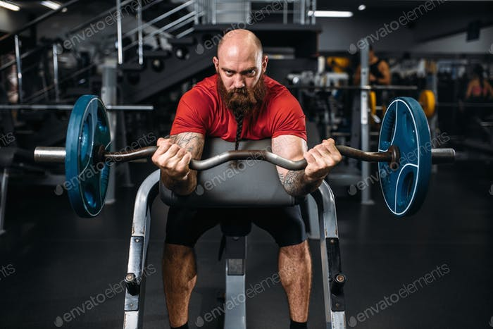 Muscular athlete doing exercise with barbell