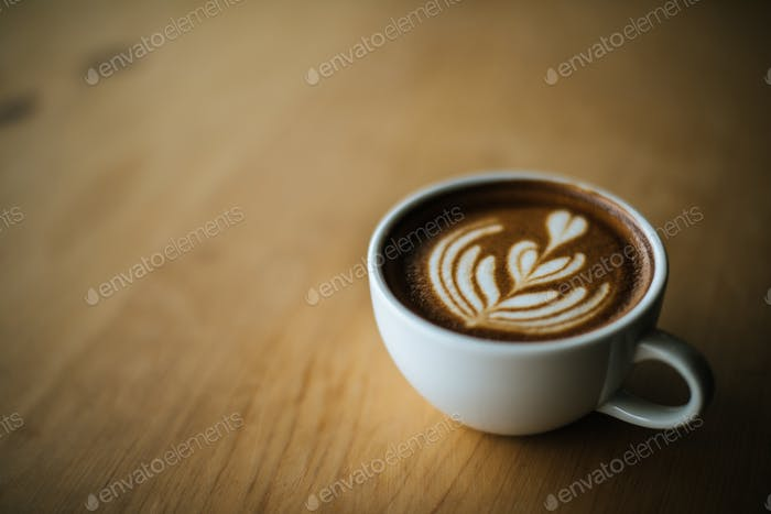Latte art in coffee cup on the cafe table