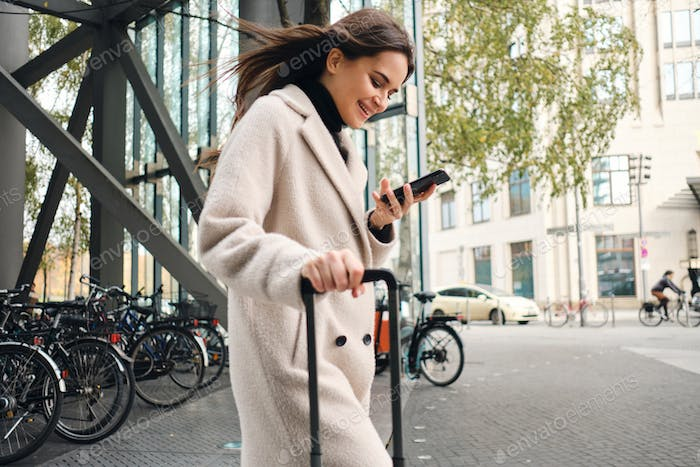 Young businesswoman in coat happily using cellphone walking through street with suitcase