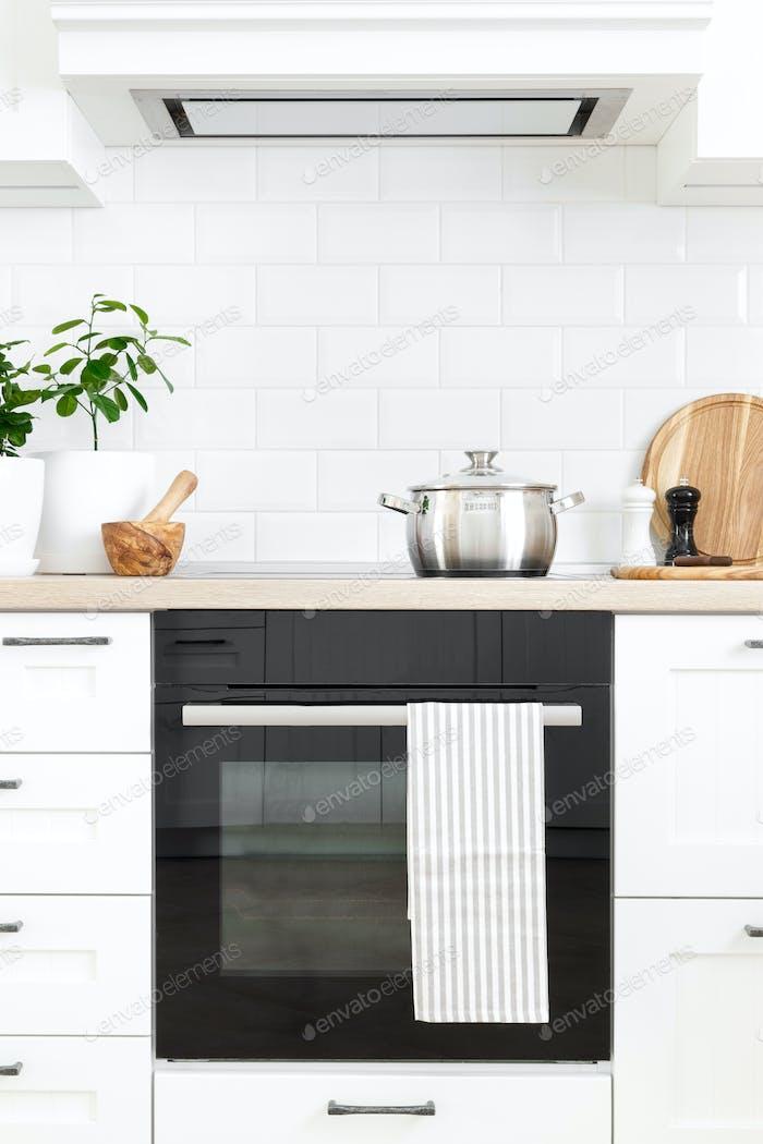 White modern kitchen interior with wooden worktop and kitchenware, culinary concept, background