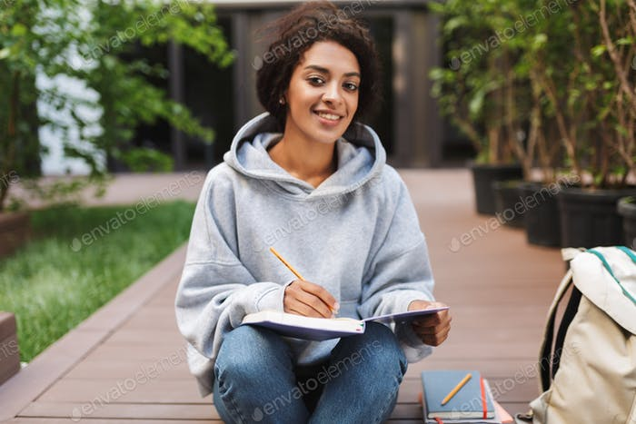 Young lady with dark curly hair sitting and making notes in notebook