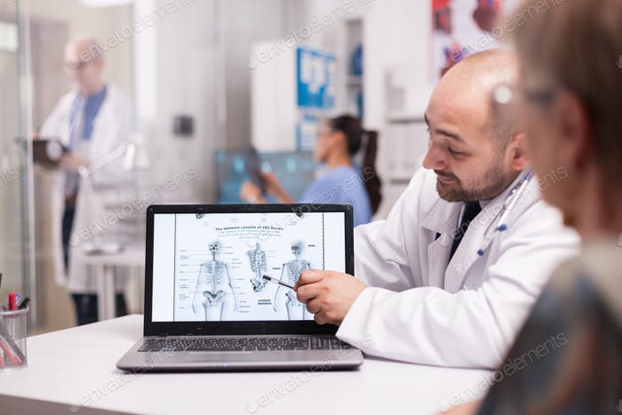 Doctor explaning back pain to senior patient