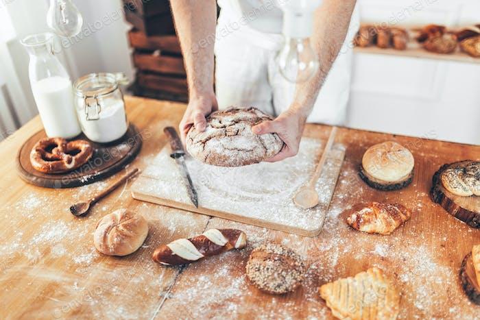 Bäcker mit einer Auswahl an köstlichen frisch gebackenen Brot und Gebäck