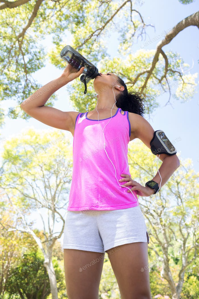 Female jogger drinking water in the park