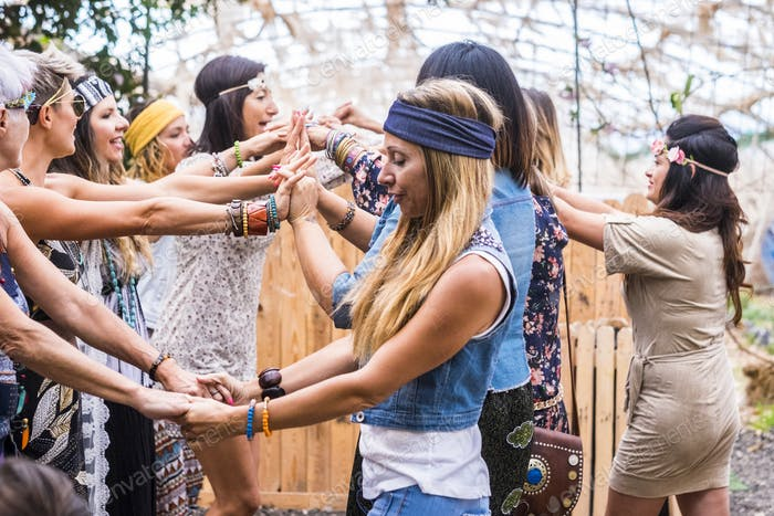 group of free and hippy rebel alternative style young women together dancing and celebrating