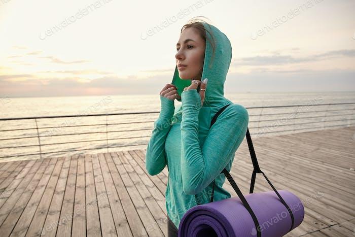 Retrato de mujer joven caminando en la orilla del mar en ropa deportiva brillante, ir a practicar yoga