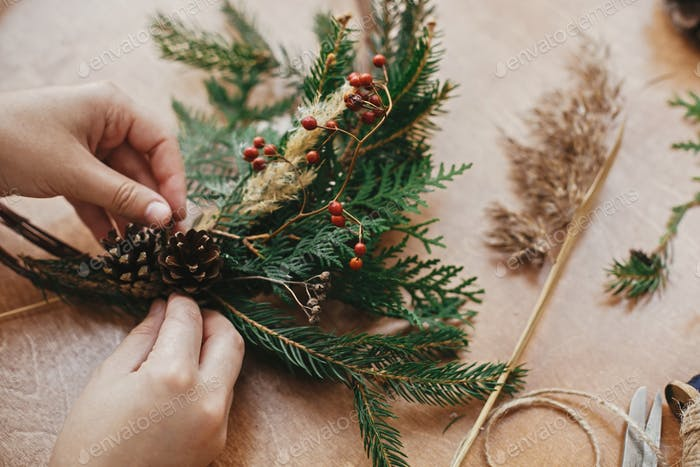 Making rustic christmas wreath. Hands holding pine cones