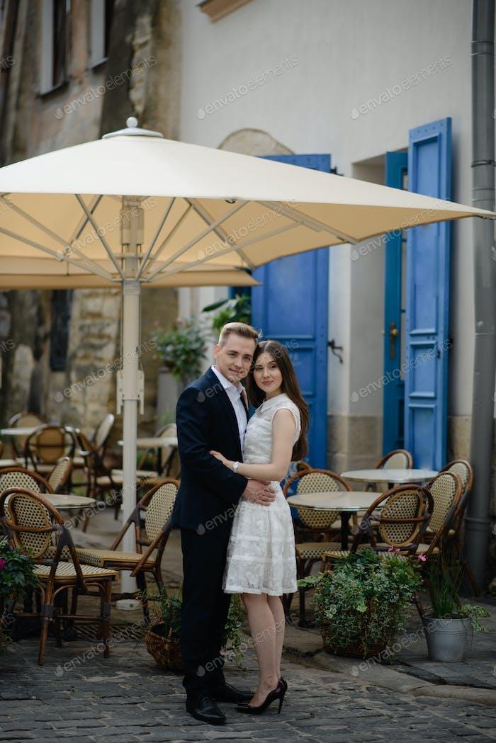 Ein lächelndes Paar genießt Getränke an einem Bartisch im Freien in der Stadt.