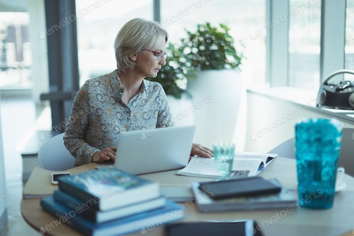 Mature businesswoman working at table