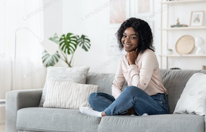 Shy Black Girl Sitting On Sofa At Home, Posing To Camera