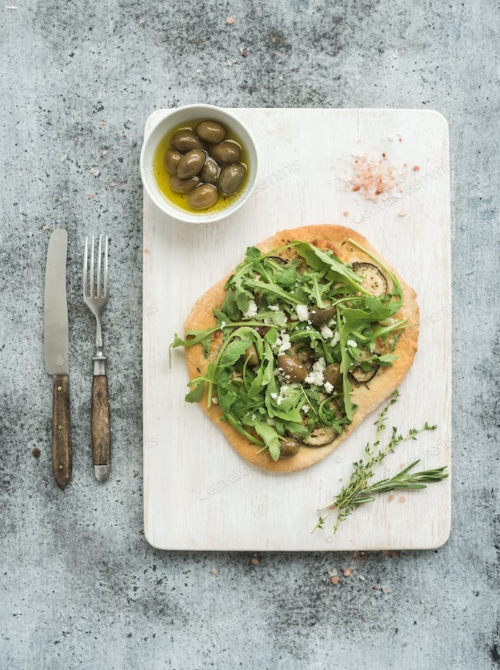 Rustic homemade pizza with eggplant, cheese, olives and arugula