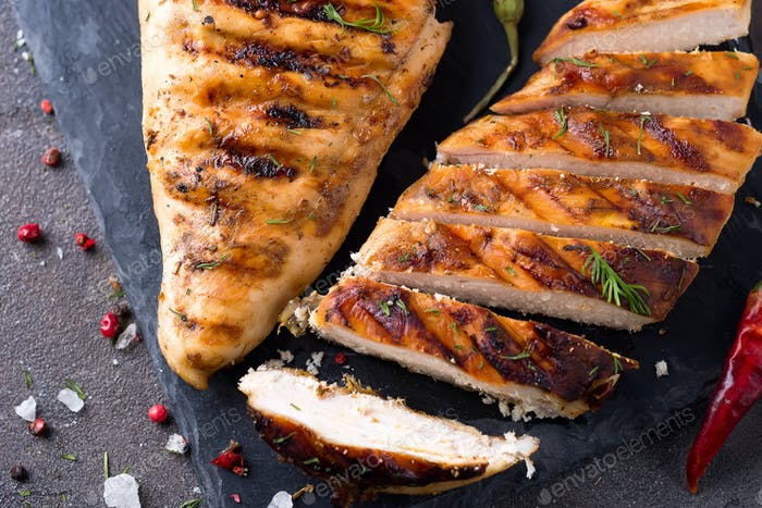 Grilled chicken fillets on slate plate on Gray concrete background. Healthy diet food concept, flat