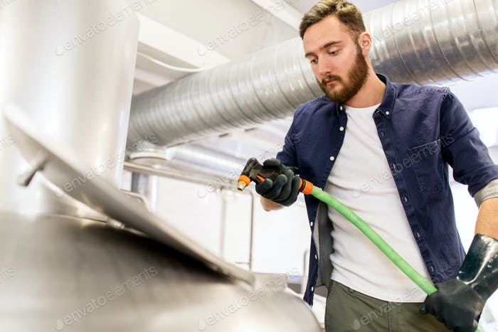 man with hose working at craft beer brewery kettle
