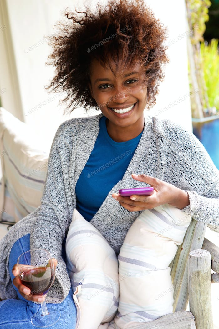 Young woman smiling with cell phone and glass of wine