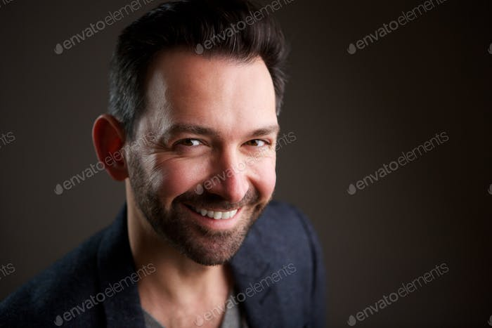 Close up handsome older man with beard posing against dark background