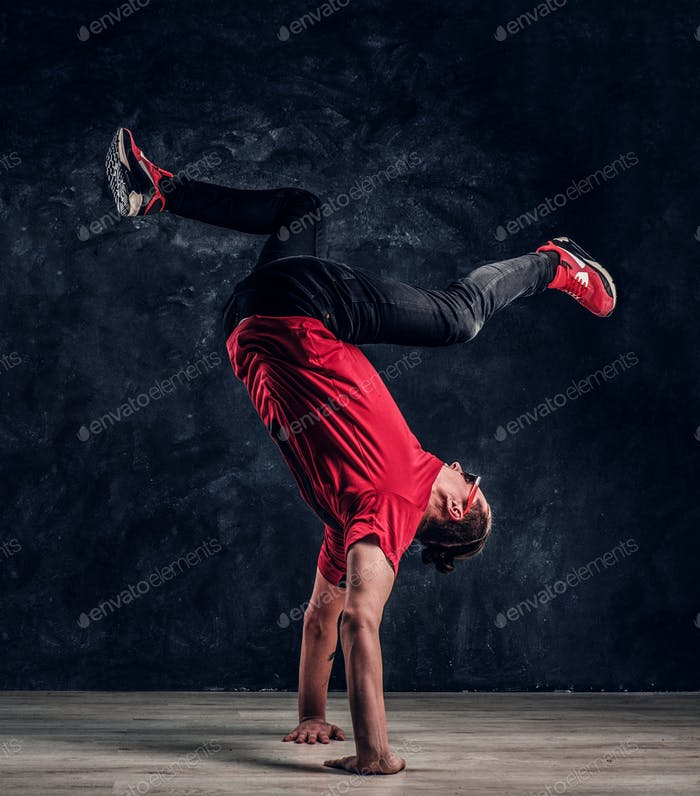 Hip-hop style dancer performs breakdance acrobatic elements.
