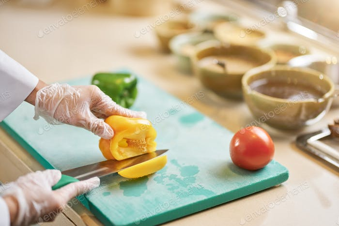 Skilled chef cutting into a fresh bell pepper