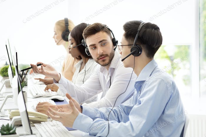 Male tech support operators communicating to solve client's request at call centre