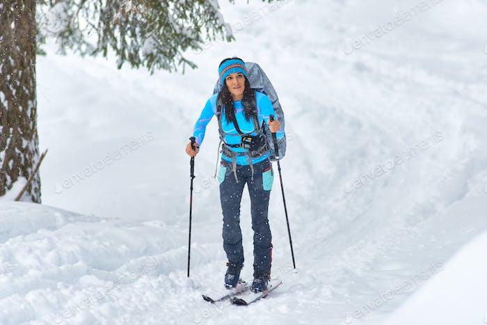 A beautiful young woman practicing hiking skiing