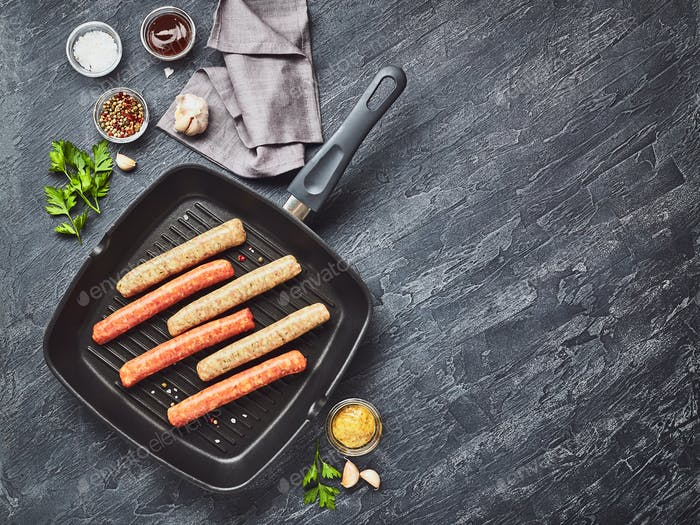 Raw meat sausages on square grill pan, with herbs and spices. Top view