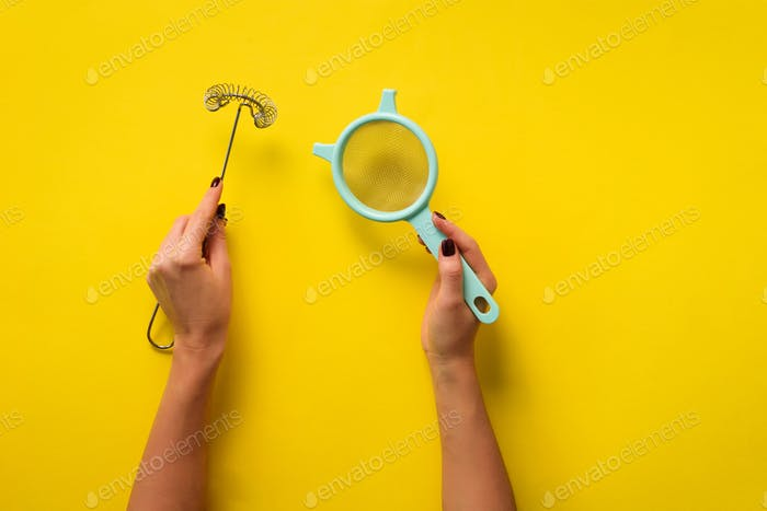 Woman hand holding kitchen utensils on yellow background. Baking tools - brush, whisk, spatula