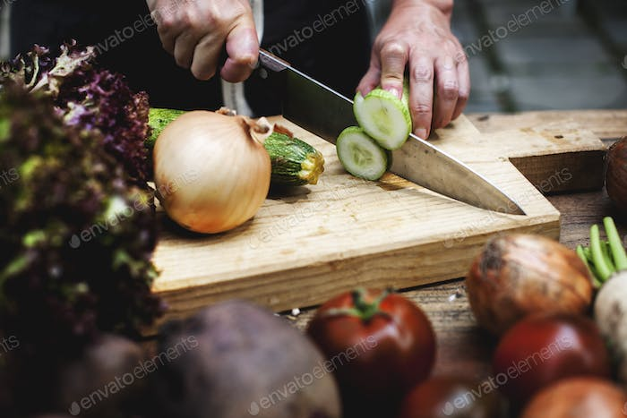 Closeup of hand with knife cutting fresh cucumber