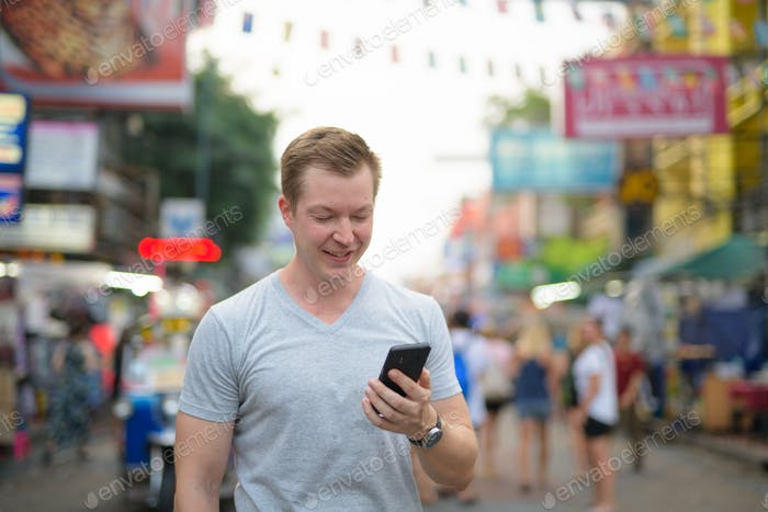 Young happy tourist man smiling while using phone against view of Khao San road in Bangkok