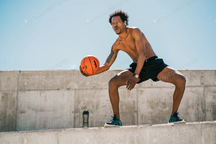 Afro athlete man playing basketball outdoors.