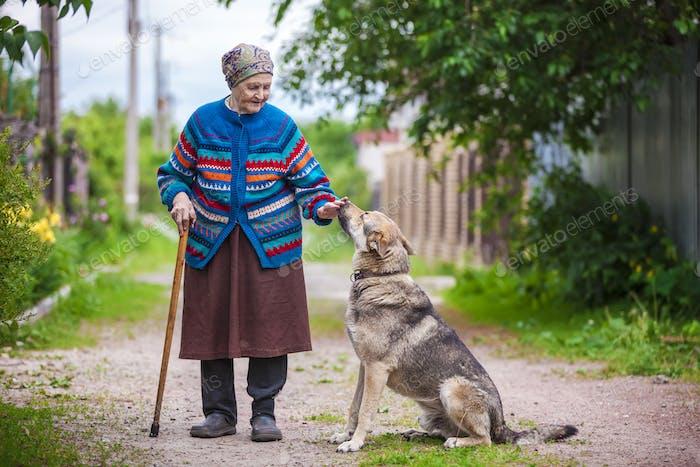 Ältere Frau mit einem Hund auf dem Land