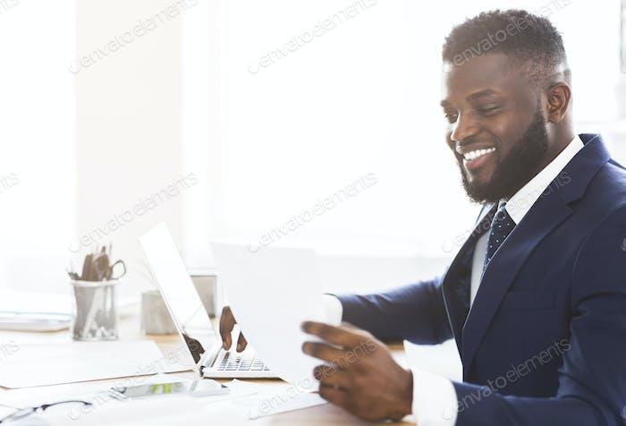 Zufriedene schwarze Geschäftsmann Überprüfung Berichte, sitzen im modernen Büro
