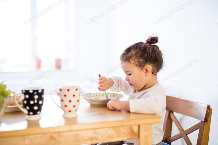 Little girl sitting at the table, eating breakfast