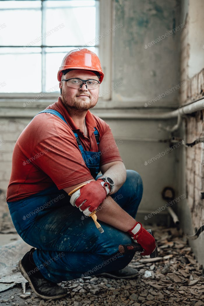 Chubby builder on a construction site working on a brick wall with a hammer