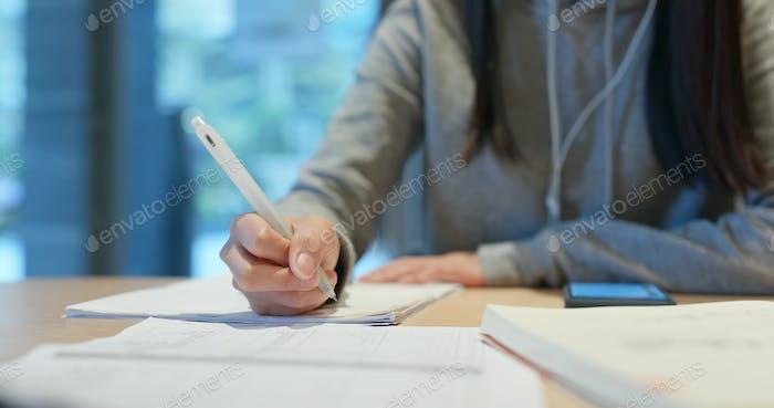 Frau studiert die Notiz auf Papier an der Bibliothek