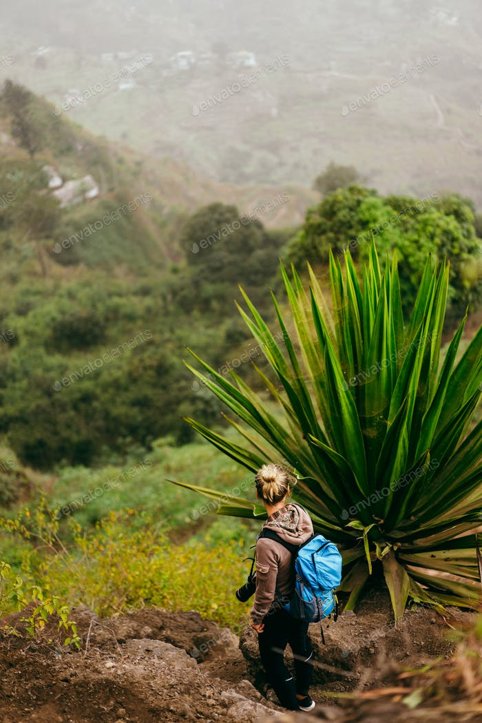 Woman with camera and backpack near one huge agave plant with arid landscape of location called