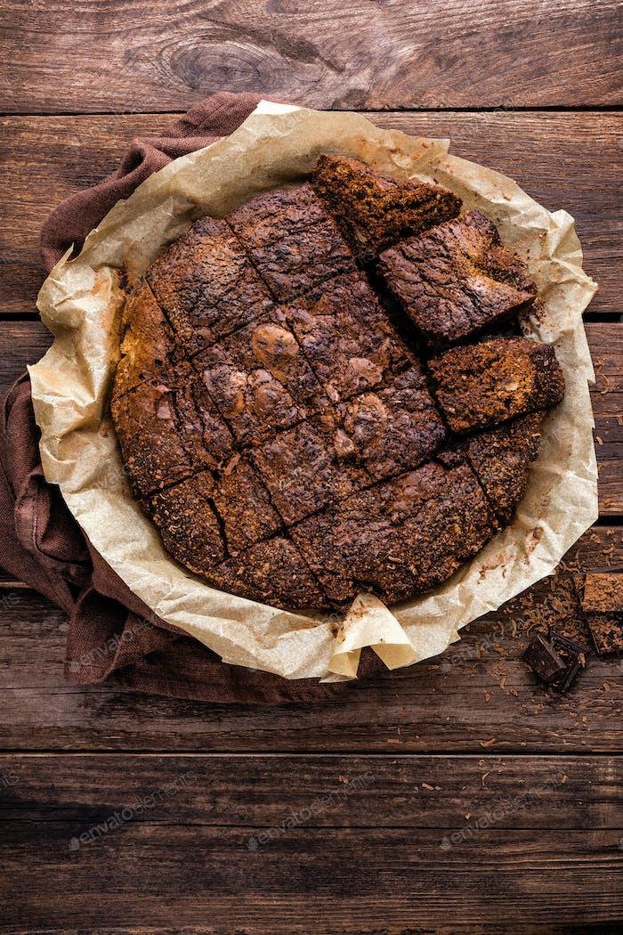 homemade chocolate brownie on dark wooden background, top view