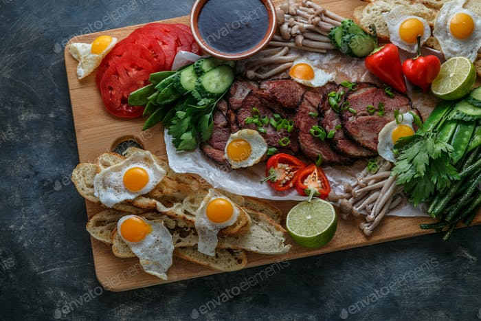 Breakfast meals variety flat lay. Top view on buffet wooden board with meat, eggs, vegetables