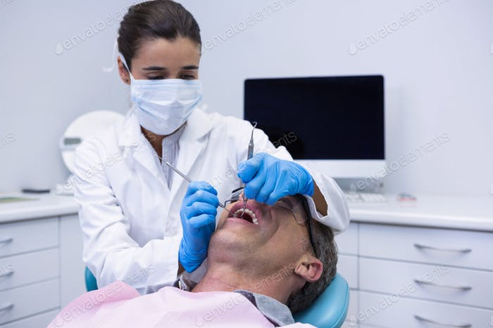Doctor giving dental treatment to patient at clinic