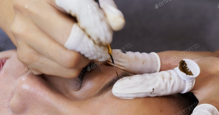 Cosmetologist applying permanent make up on woman eyebrow