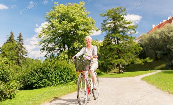 happy senior woman riding bicycle at summer park