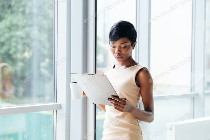 Beautiful african young businesswoman holding clipboard and reading in office
