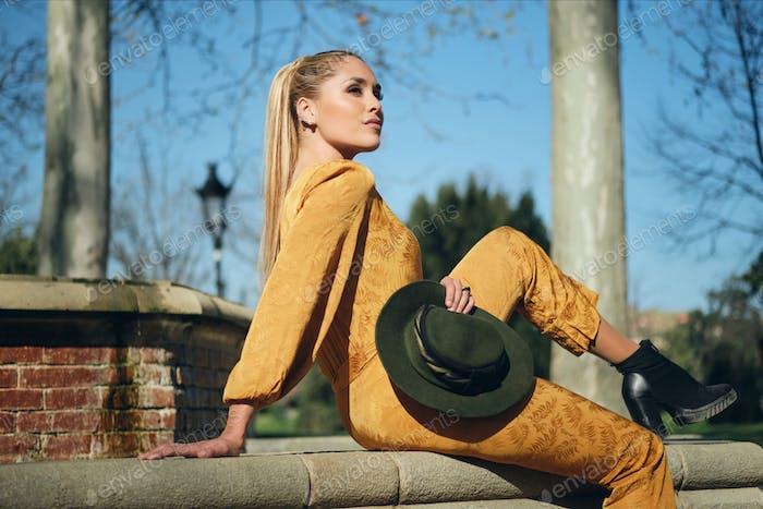 Mujer joven hermosa y elegante en un mono naranja con sombrero posando con confianza en la cámara