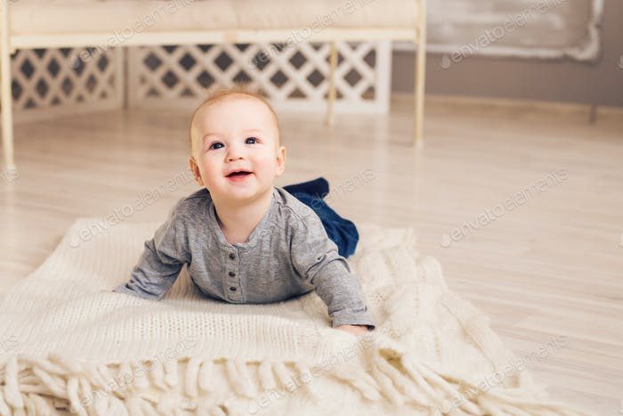 Adorable baby boy in sunny bedroom