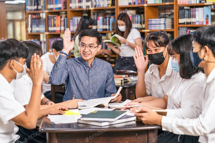 Asian teacher raising hand and Giving Lesson to group of College Students for answer question
