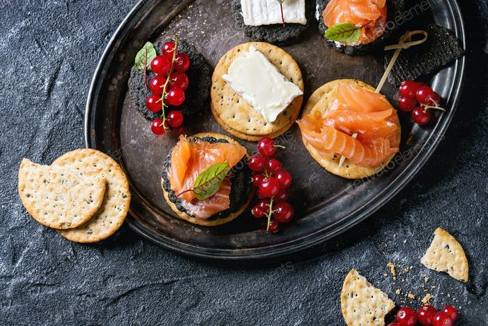 Black crackers with salmon and berries