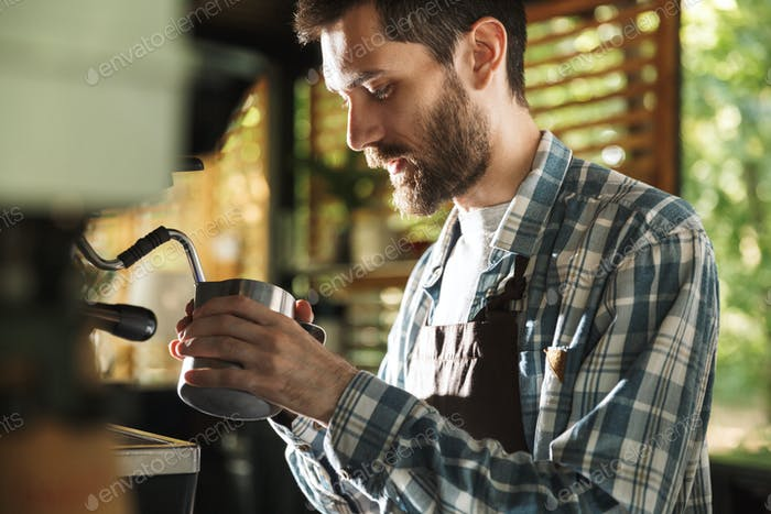 Image of professional barista boy making coffee while working in