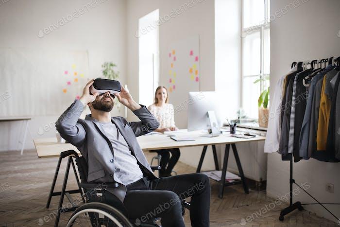 Zwei Geschäftsleute mit Rollstuhl und VR-Brille im Büro.